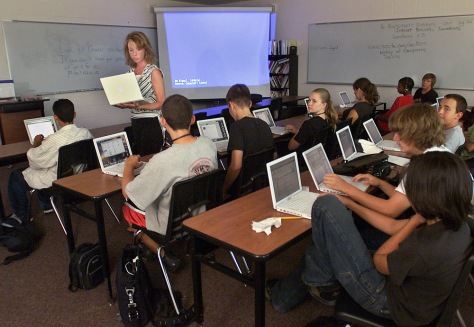 Teacher instructs laptop-using students