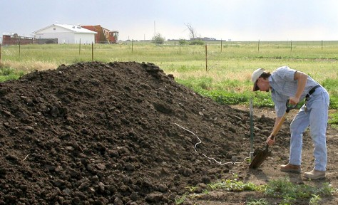 IMAGE: STUDENT DIGS THROUGH MANURE