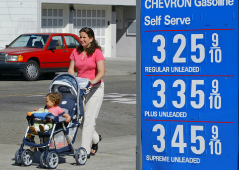 A woman pushes a baby in a stroller past a gasoline price sign in San Francisco