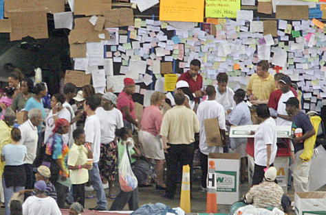 Refugees from Hurricane Katrina mill about near message boards in the Houston Astrodome