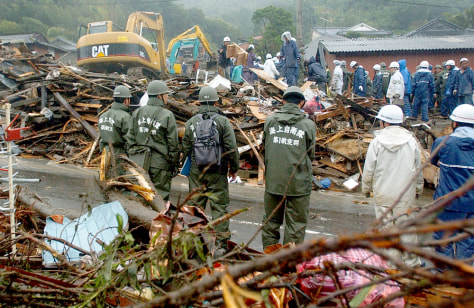 Image: Rescuers search for survivors in the debris of houses destroyed by a heavy mud slide in Tarumizu, southern Japan