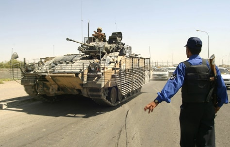 Imgae: A British tank drives past an Iraqi policeman in the southern city of Basra on Thursday.