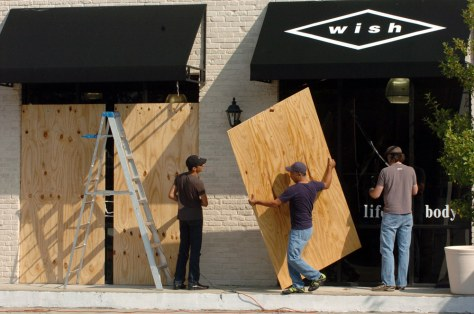 Workers take down protective plywood at a store in Houston.