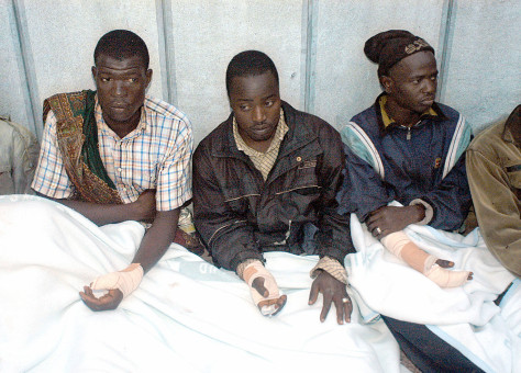 Image: Wounded African immigrants sit outside the hospital in Ceuta after a mass overnight charge on the borders of the Spanish enclave on Thursday.