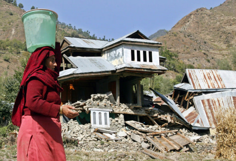 Kashmiri quake survivor carries water past destroyed house