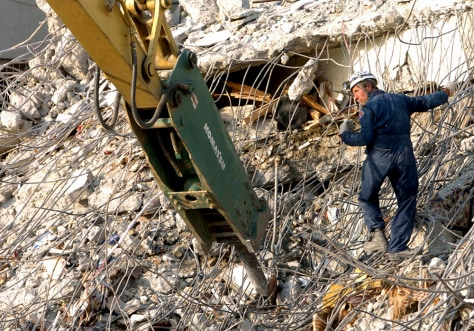 A rescuer from the United Kingdom directs a crane operator in a bid to find trapped people in the rubble of the high-rise Margalla Towers in the Pakistani capital, Islamabad.