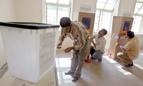 Iraqi voting station employees install elections material at a voting station in Basra