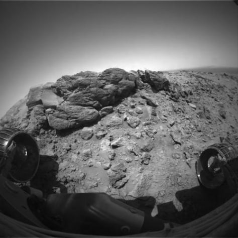 "Spirit climbs atop rock outcrop at the summit of ""Husband Hill"" on Mars."