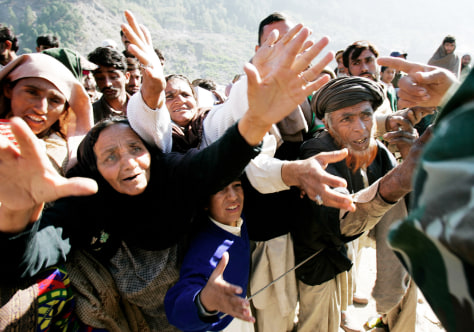 PAKISTANI EARTHQUAKE SURVIVORS REACH FOR RELIEF GOODS