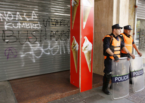 Argentine police officers stand outside a Mar del Plata fast food restaurant boarded up in anticipation of protests at the Summit of the Americas.