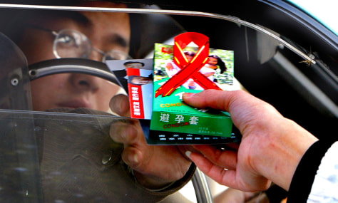 Image: Volunteer hands condoms and AIDS brochures to a driver