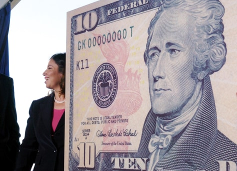 U.S. Secretary of the Treasury John Snow and U.S. Treasurer Anna Escobedo Cabral talk near a sample ten dollar note