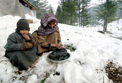 Image: Indian Kashmiri woman and child do laundry in the snow.