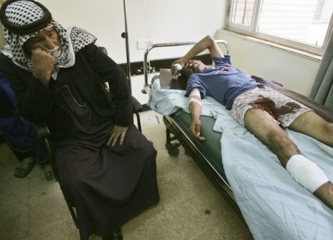 Image: A man sits with his son who was wounded on Tuesday, in a suicide bomb attack on a Baghdad police academy.