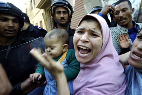 Image: An Egyptian woman shouts as policemen block voting station.