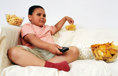 Boy Watching Television Surrounded by Junk Food