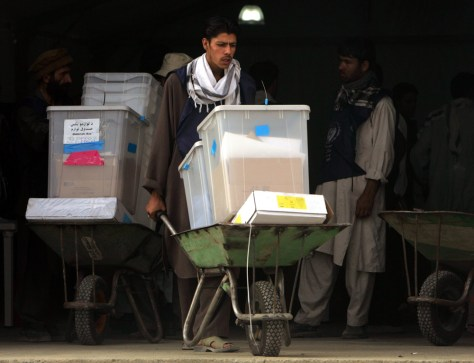 Image: Afghan election workers move ballot boxes into a Kabul store on Monday.