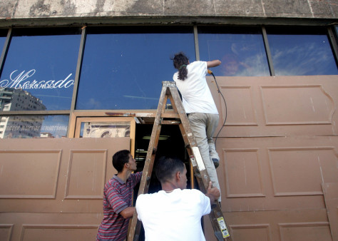 Workers cover the windows of a supermarket in Havana