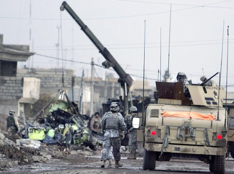 Crane removes wreckage of U.S. OH-58D Kiowa Warrior helicopter in Mosul