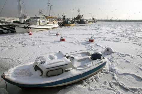 Snow-covered fishing and sailing boats are seen on the frozen Baltic Sea in Hel