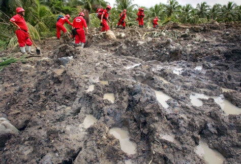 Members of a rescue team from Taiwan walk on rocks and mud after landslide buried Guinsaugon village in central Philippines
