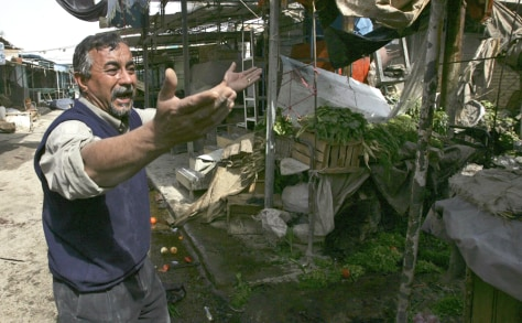 Image: An Iraqi resident reacts angrily to the destruction of his market shop by a roadside bomb in Baghdad on Thursday.