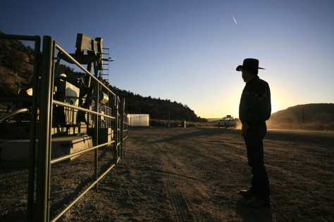 IMAGE: RANCHER WATCHES OIL FIELD TRUCK