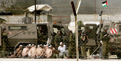 Image: Israeli soldiers guard Palestinian prisoners.