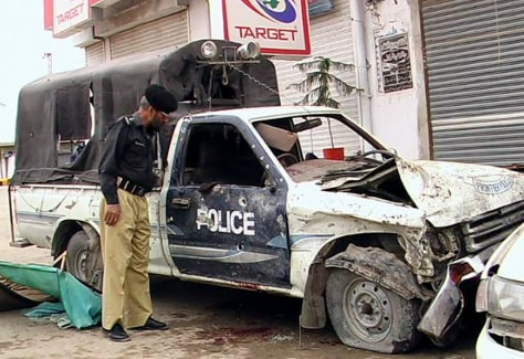 A Pakistani policeman inspects a damaged police vehicle in Pakistan