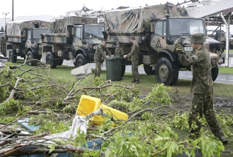 Image: Soldiers from the Australian Army in Innisfail help clean up on Tuesday after Cyclone Larry devastated the region.