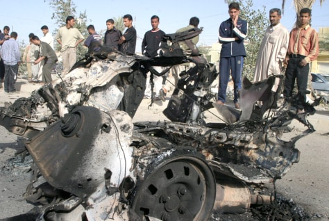 Local residents view remains of vehicle after suicide car bomb attacked US military convoy in Falluja