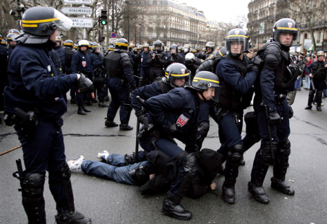 French riot police apprehend a youth during clashes at end of protest in Paris