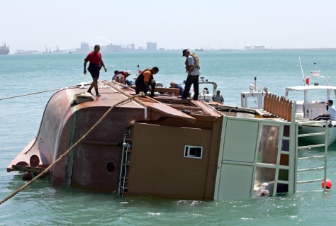 Image: Rescue workers stand on the wreckage of the capsized tourist boat