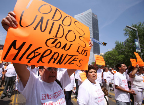 Mexicans hold placards during march in Mexico City in favour of migrants in the U.S.