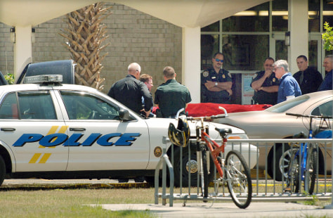 Funeral home personnel remove the body of a shooting suspect that committed suicide in front of a school in Fernandina Beach