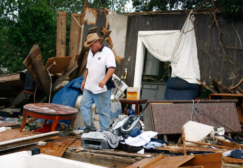 IMAGE: MAN SURVEYS DAMAGED HOME