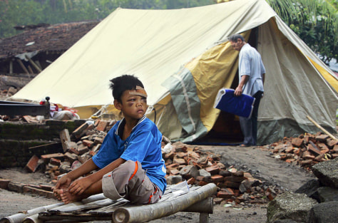 INJURED BOY SITS OUTSIDE TENT