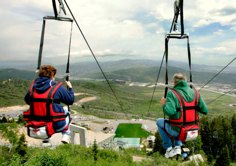 Image: Two people ride zip line.
