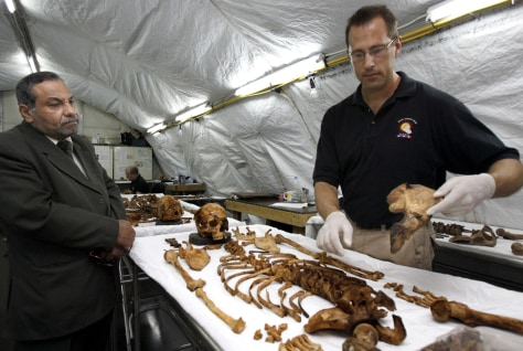 Image: A forensic expert, right, gathers the bones of a human being