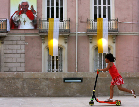 A girl rides a scooter in front of a poster of Pope Benedict XVI in Valencia, Spain