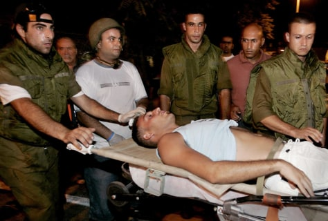 A wounded Israeli man is rushed from the scene of a rocket attack in the northern Israeli town of Haifa