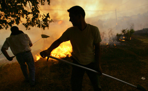 Villagers try to extinguish a fire in the village of Ponte Bora, northwestern Spain, on Aug. 7