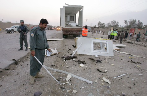 Afghan policeman investigates at a blast site in Kabul