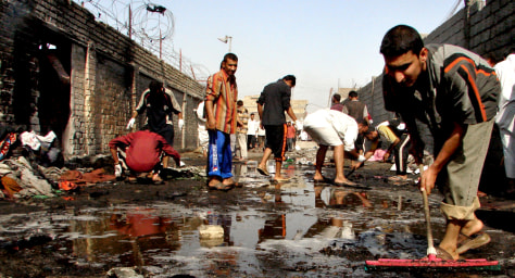 Iraqi civilians inspect the site of a bo