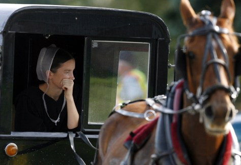 An Amish woman looks out from her wagon at the scene of the Georgetown school shooting in Nickel Mines near Lancaster, Pennsylvania