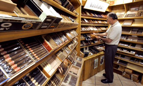 Image: Gary Bahrenfus arranges cigars in store