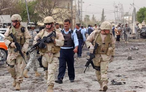 US soldiers and Iraqi police secure the scene of a suicide car bomb attack in Kirkuk