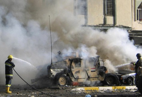 Firemen hose down an Iraqi armoured vehicle after a suicide car bomb attack in Kirkuk
