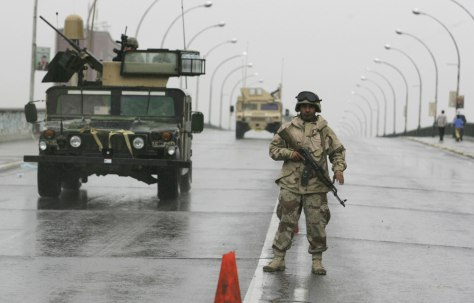 Image: A soldier stands guard as U.S. armored vehicles patrol a Baghdad road