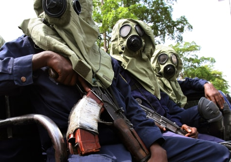 Congolese riot police in gasmasks ride on a vehicle along the streets of Kinshasa